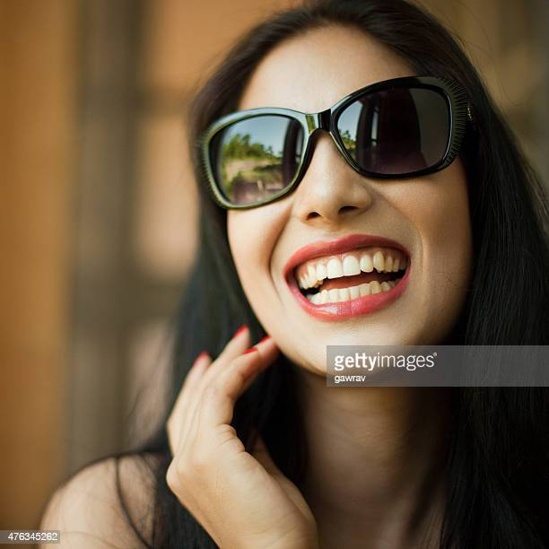 Attractive young woman in sun glasses laughing out loud.