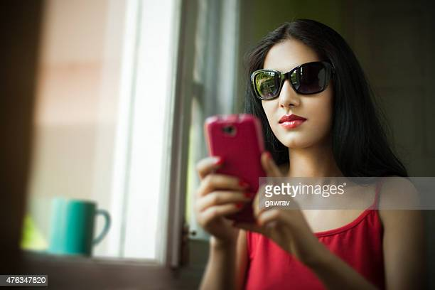 Attractive, young woman in sunglass near window using smart phone.
