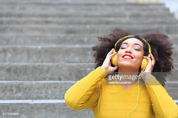 Jolie jeune femme écoutant de la musique dans la zone jaune sspace-copy