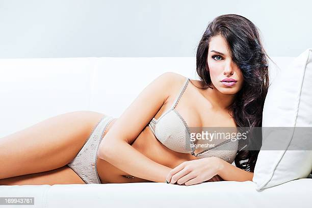 Attractive young woman leaning  on a sofa.