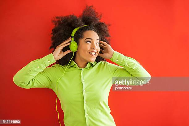 Attractive young woman listening music on red background