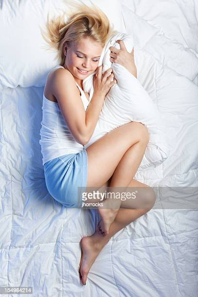 Attractive Young Woman on Bed Hugging Pillow