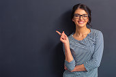 Attractive girl in casual clothes and eyeglasses is pointing away, looking at camera and smiling, standing against dark background