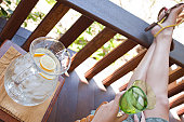 Attractive Young Woman Relaxing on Porch of American Craftsman Style House with Pitcher of Ice Water, Detail
