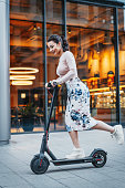 Attractive young woman riding contemporary kick scooter at cityscape background.