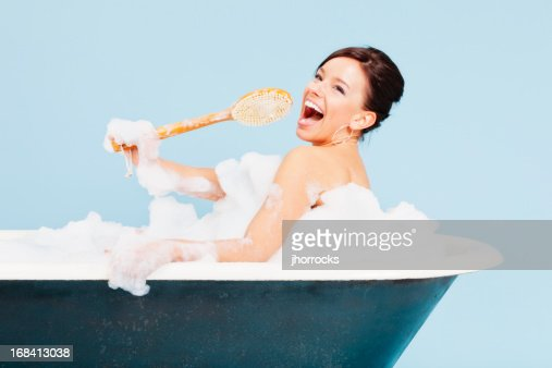 Attractive Young Woman Singing In Bath Tub Stock Photo