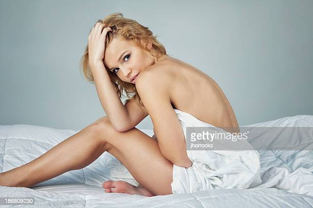 Attractive Young Woman Sitting on Bed Wrapped in Sheets