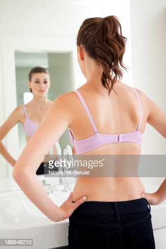 Attractive young woman standing in front of mirror : Stock Photo