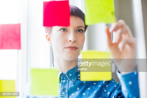 Attractive young woman viewing post-it notes