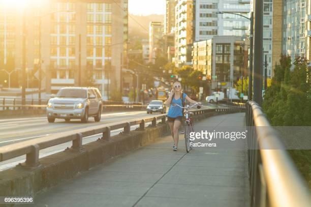 Attraktive junge Frau geht auf Bürgersteig Fahrrad an einem sonnigen Nachmittag