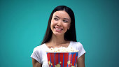 Attractive young woman with big cup of popcorn smiling and flirting in cinema