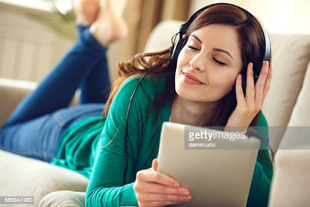 Attractive young woman with headphones listens music on digital