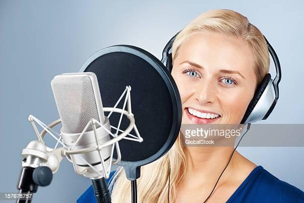 Attraktive junge Frau mit Mikrofon und Lächeln