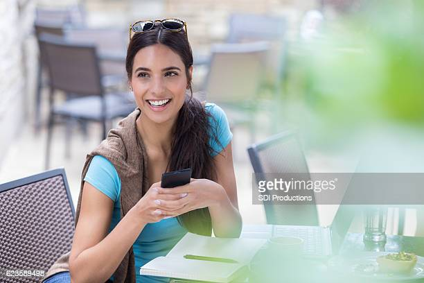 Attractive young woman with smart phone at outdoor cafe