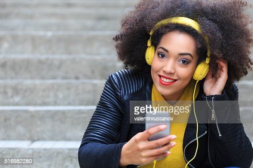 Attractive young woman with yellow headphones-copy space