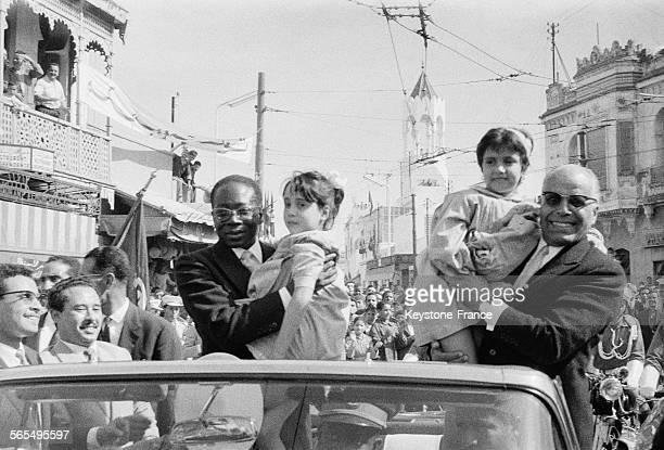 Au cours de la traversée de la capitale les Présidents Senghor à gauche et Bourguiba à droite dans leur voiture tiennent dans leurs bras deux...