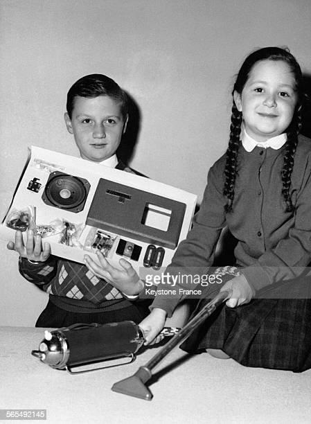 Au Salon de l'Enfance les enfants ont élus leurs jouets préférés et les deux membres du jury montrent les premiers prix pour les garçons un poste de...
