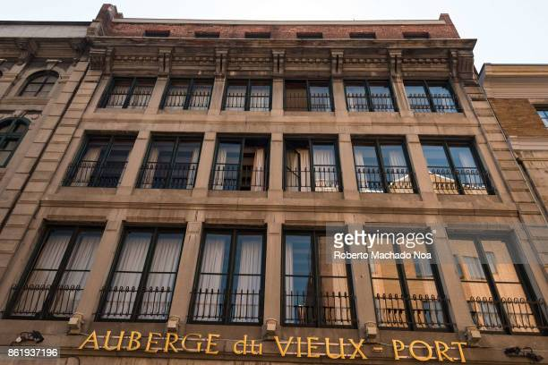 Auberge du VieuxPort hotel facade golden metal signage is on face of the period building having rows of balconies and glass doors