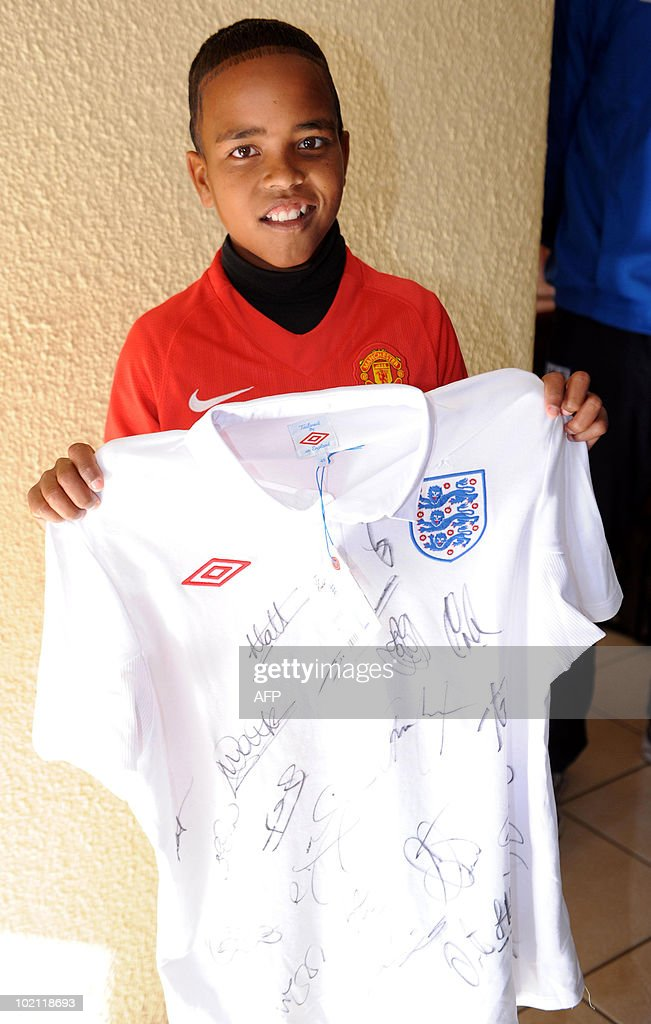 Aubrey, aged 12 poses with England's national team shirt as part of a visit by England's national team players Matthew Upson and Michael Dawson to an orphanage in the Tlhabane Township near, Rustenburg on June 15, 2010.