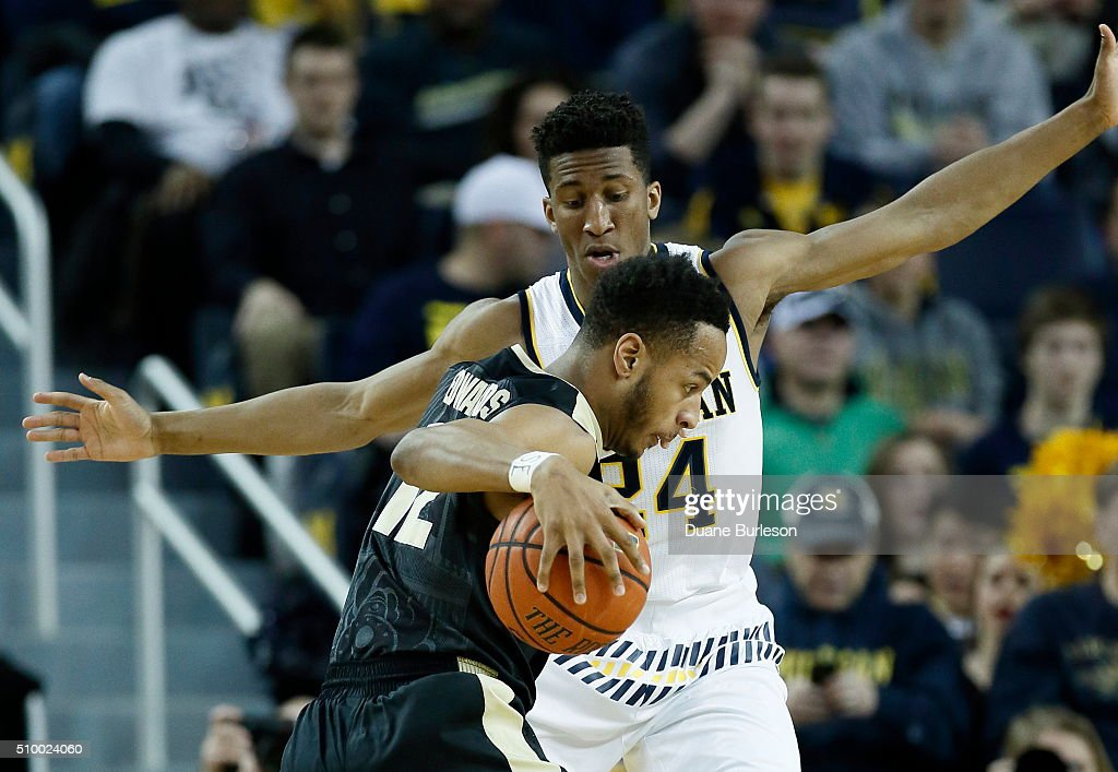 Aubrey Dawkins #24 of the Michigan Wolverines guards Vince Edwards #12 of the Purdue Boilermakers during the first half at Crisler Arena on February 13, 2016 in Ann Arbor, Michigan.