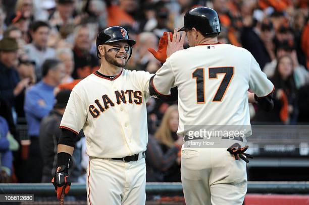 Aubrey Huff of the San Francisco Giants celebrates with Cody Ross after scoring against the Philadelphia Phillies on a double by Buster Posey in the...