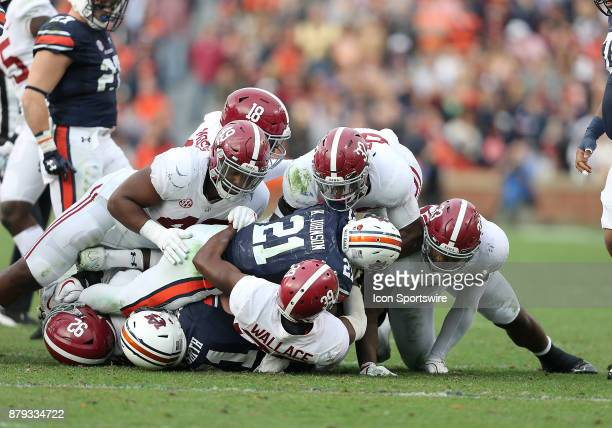 Auburn Tigers running back Kerryon Johnson is tackled by Alabama Crimson Tide linebacker Rashaan Evans and teammates during a football game between...