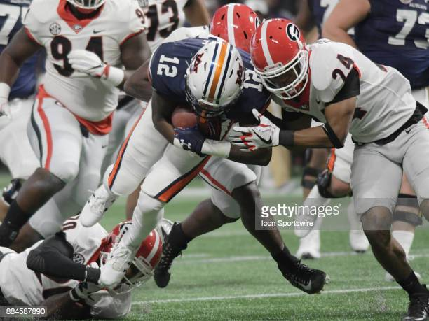 Auburn Tigers wide receiver Eli Stove rushes the ball as Georgia Bulldogs defensive back Dominick Sanders tackles him during the SEC Championship...