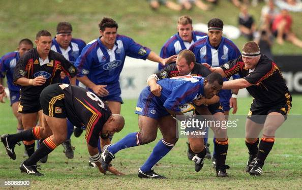 Auckland Blues Joeli Vidiri leads a charge forward as he is tackled by Waikato Chiefs Paul Martin and Koula Tukino during their Super 12 match played...