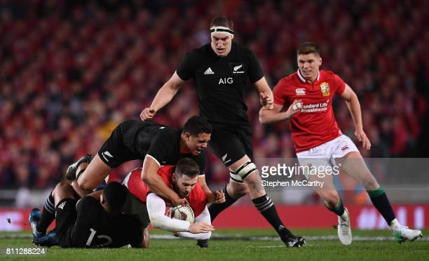 Auckland New Zealand 8 July 2017 Elliot Daly of the British Irish Lions is tackled by Ngani Laumape and Anton LienertBrown of New Zealand during the...