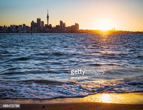 Auckland skyline at sunset from Devonport beach