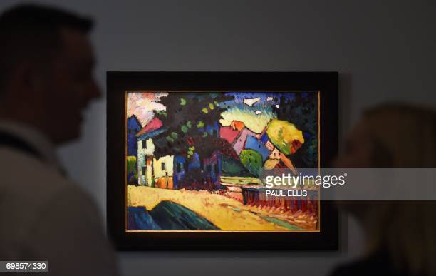 Auction house employees look at Russian artist Wassily Kandinsky's oil painting 'Murnau Landschaft mit grunem haus' estimated to fetch between 1525...