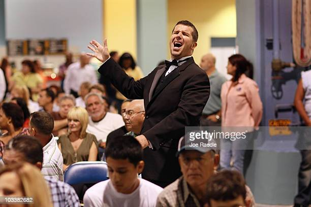 Auction ringman Brett Baugh reacts while taking bids during the Fannie Mae foreclosed home auction at the Miami Beach Convention Center on August 14...