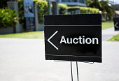 Auction sign, outside suburban home, positioned on front lawn.