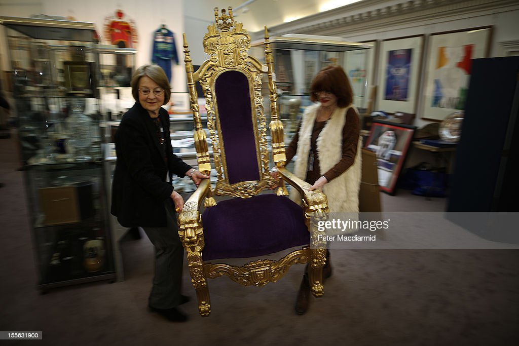 Auction staff move the Bradley Wiggins London 2012 Olympics golden throne into place at Sotheby's on November 6, 2012 in London, England. Graham Budd auctioneers are holding a two day sale of Sporting Memorabilia at Sotheby's in London on 5-6th November 2012.