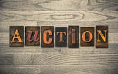 """The word """"AUCTION"""" theme written in vintage, ink stained, wooden letterpress type on a wood grained background."""