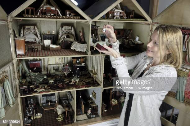 Auctioneer Catrin Hampton checks miniature china from a Victorian doll's house which is to be auctioned at Chorley's in Gloucestershire on 28...