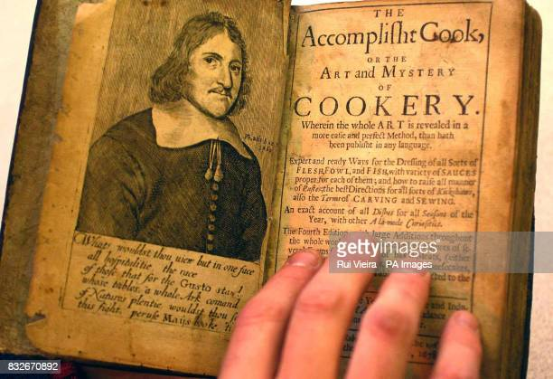 TV auctioneer Charles Hanson holds open The Accomplished Cook the Art and Mastery of Cookery book which dates back to 1678 printed 12 years after the...