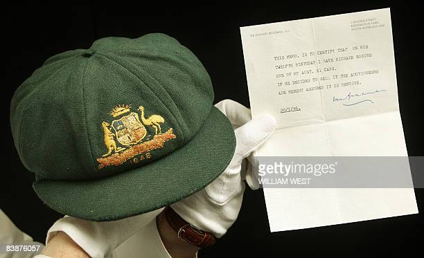 Auctioneer Charles Leski holds the 1948 'Baggy Green' cap worn by Australian cricketing legend Don Bradman in his last Test match and which is up for...