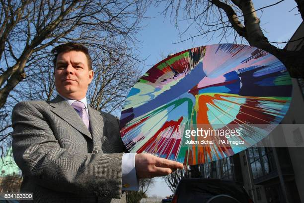 Auctioneer Garrett O'Connor in Dublin holding the prized Damien Hirst painting which gained notoriety after selling at an anonymous auction for just...