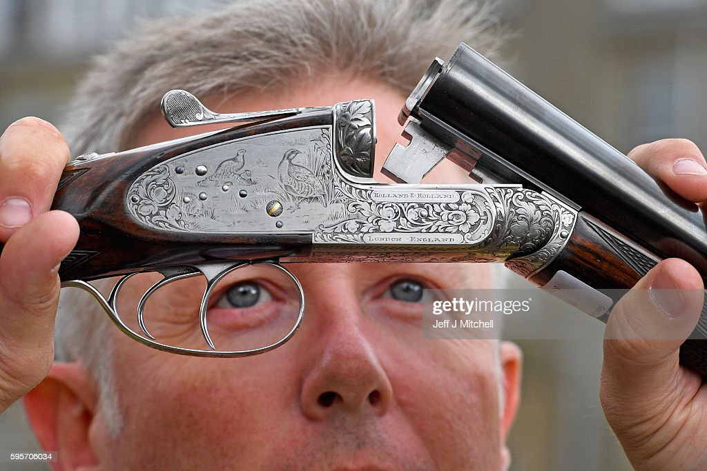 Auctioneer Gavin Gardiner holds a 12bore 'Royal de Luxe' model selfopening sidelock ejector gun by Holland and Holland at Gleneagles Hotel on August...