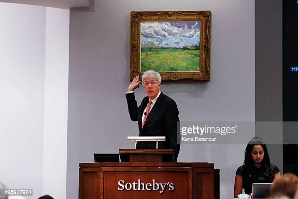 Auctioneer Henry Wyndham shows a Vincent Van Gogh artwork titled 'Paysage sous un ciel mouvementé' as it is auctioned at Sotheby's for $54000 on...