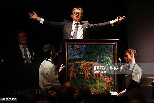 Auctioneer Jussi Pylkkanen gestures behind a painting by Erich Heckel entitled 'Badende am Waldteich' during the Impressionist and Modern Evening Art...