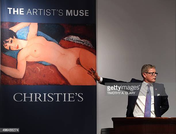 Auctioneer Jussi Pylkkanen gestures towards a picture of Amedeo Modigliani's 'Nu couche' during the 'Artist Muse A Curated Evening Sale' November 9...