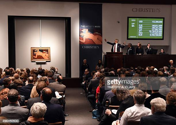 Auctioneer Jussi Pylkkanen holds his hands up as he sells Amedeo Modigliani's 'Nu couche' during the 'Artist Muse A Curated Evening Sale' on November...
