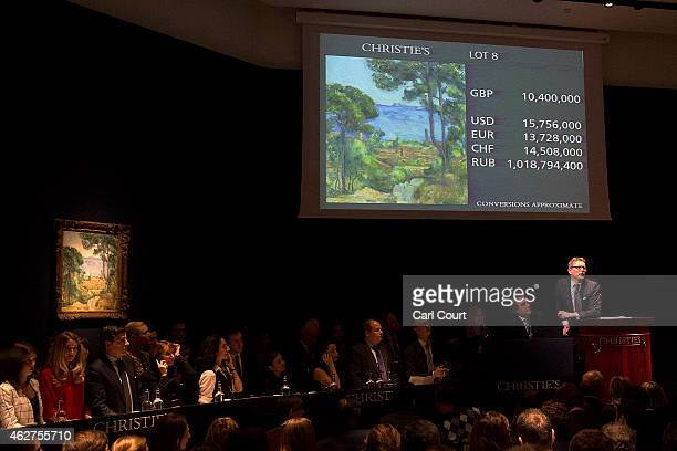 Auctioneer Jussi Pylkkanen takes bids for Vue sur L'Estaque et le Chateau d'If by Paul Cezanne at Christies on February 04 2015 in London England...
