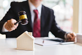 Auctioneer knocking down a model house with his gavel, Property sale auction concept