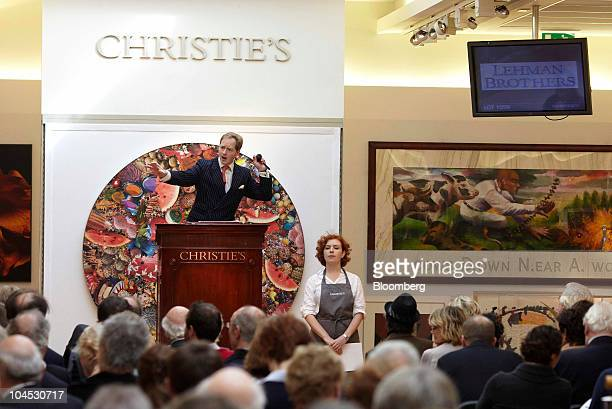 Auctioneer Nick Martineau stands on the podium surrounded by artwork from the Lehman Brothers collection during the auction at Christie's...