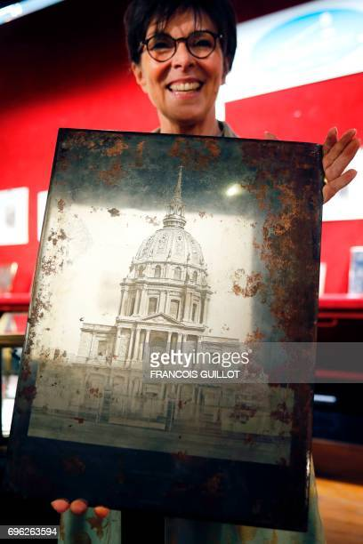 Auctioneer Patricia CasiniVitalis poses on June 15 in Paris with a photoengraving by Edouard Baldus depicting the Hotel des Invalides which will be...