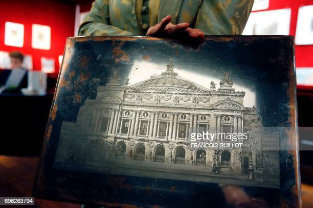 Auctioneer Patricia CasiniVitalis poses on June 15 in Paris with a photoengraving by Edouard Baldus depicting the Garnier Opera House which will be...
