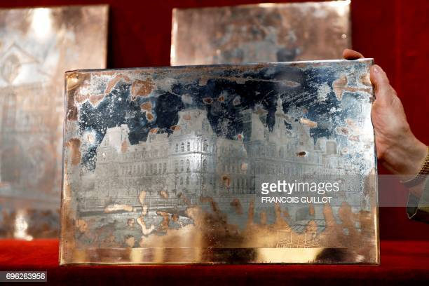 Auctioneer Patricia CasiniVitalis poses on June 15 in Paris with a photoengraving by Edouard Baldus depicting the City Hall of Paris which will be...